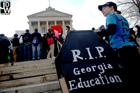 student protestor holds a casket reading RIP Georgia Education