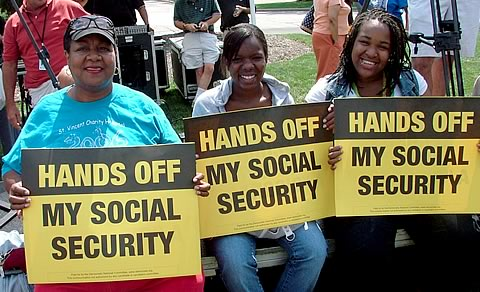 Women hold signs reading HANDS OFF SOCIAL SECURITY