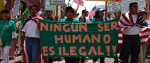 Immigrant activists hold sign reading Ningun Ser Humano Es Ilegal